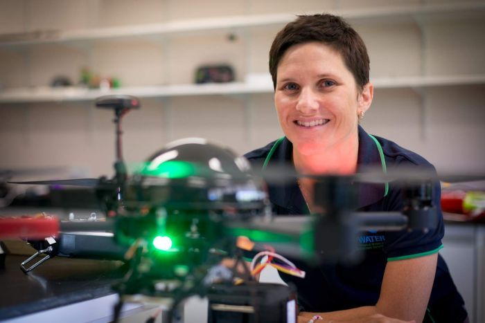 Dr Karen Joyce peers at the camera from behind a drone in her indoor hangar at James Cook University's Cairns campus.
