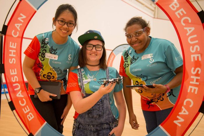 A group of three teenage girls pose with a drone inside one of the obstacle course loops they have learned to fly through.