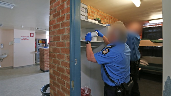 Guards conduct a search of a cell.