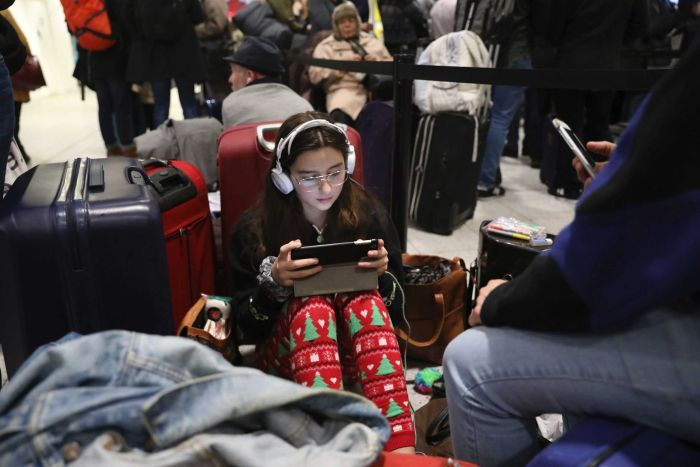 A young girl sits on the ground in side Gatwick airport using an iPad with headphones on.