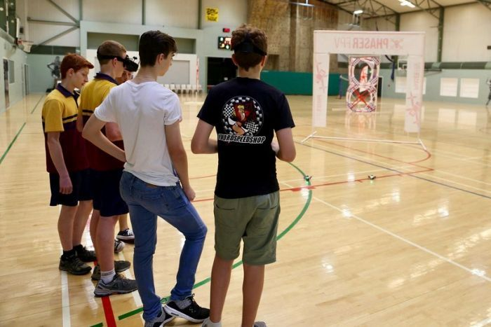 A group of people race drones inside a sports hall