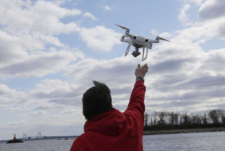 FILE - In this April 29, 2018, file photo, a drone operator helps to retrieve a drone after photographing over Hart Island in New York. Drone sightings reported by airline pilots over New Jersey renew questions about how to accommodate the popular devices into the nation's airspace. The ability of drones to interfere with aviation is likely to get worse as the number of machines multiplies. Many store-bought drones come with technology to prevent owners from flying them near airports, but there are hacks, and home-built machines don't necessarily include those protections. Photo: Seth Wenig, AP / Copyright 2019 The Associated Press. All rights reserved.