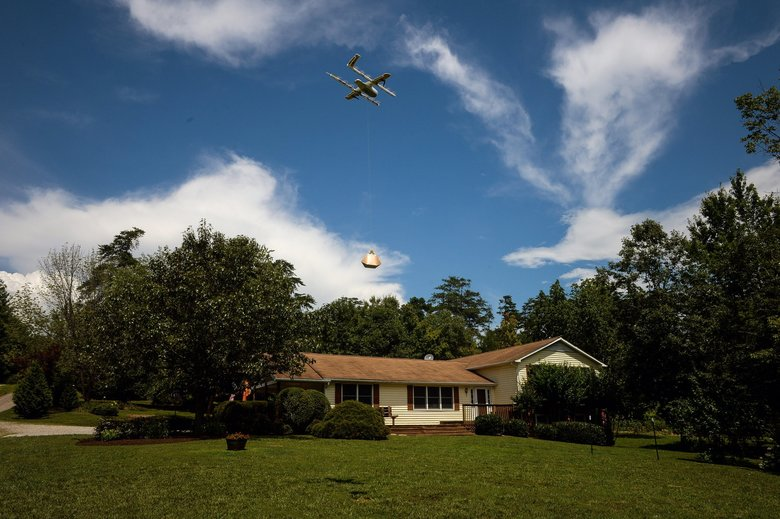 A drone from Alphabet's Project Wing unit delivers a package at a home during a demonstration in Blacksburg, Virginia, last year. (Charles Mostoller / Bloomberg)