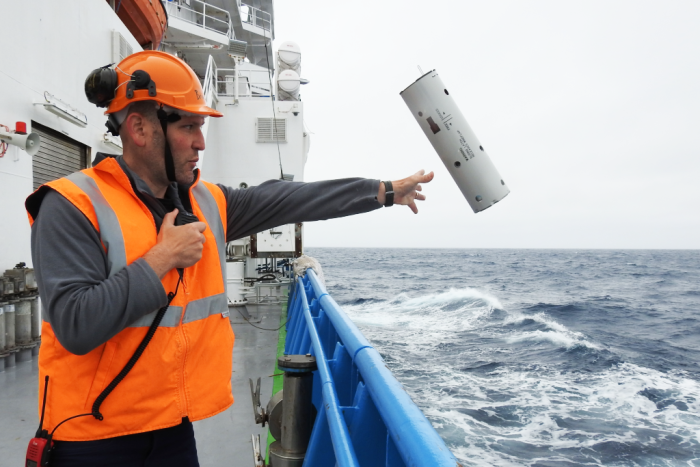 Brian Miller deploying a sonobuoy listening device off the Investigator near Antarctica
