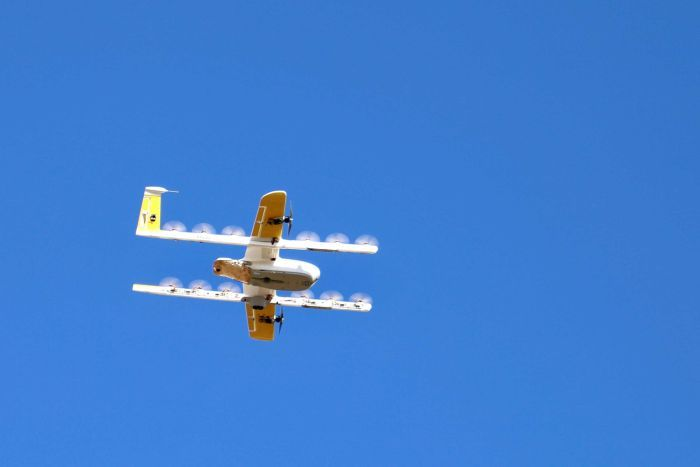 A drone, which looks like a small plane, flies through a blue sky.